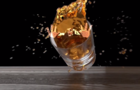Man rolling from a glass full of whisky